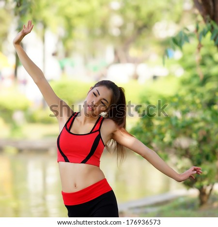 Young pretty woman doing yoga exercises in the park
