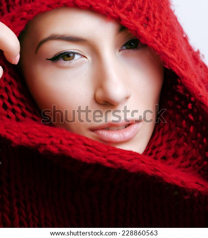 young pretty woman in sweater and scarf all over her face close up