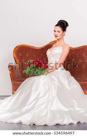 Young pretty woman in white wedding dress posing indoor in white vintage interior with bouquet