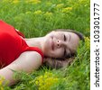 Young pretty woman lying on green grass - stock photo