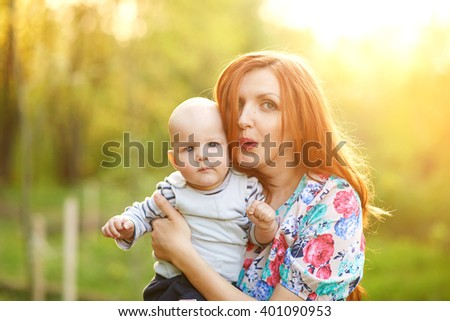 Young pretty woman stands on a background of the forest, holding a child and looking at the camera