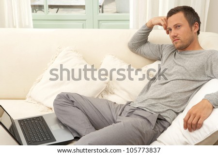 Young professional man using a laptop computer while sitting on a white sofa at home.