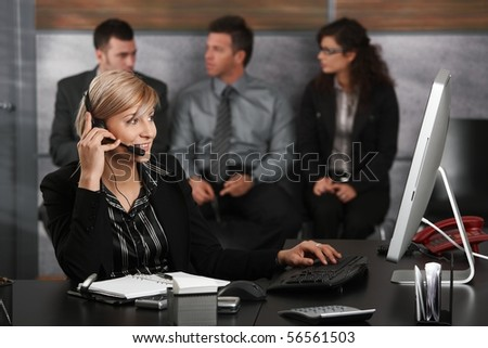 Young receptionist sitting at desk in office recepcion, talking on mobile phone, smiling, people waiting in background.