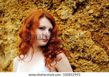Young redhead sensual woman portrait standing near the rock. Outdoor.