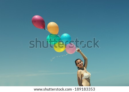 Young redhead woman holding colorful balloons