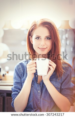 Young redhead women with white cup of coffee sitting near the mirror in dressing room