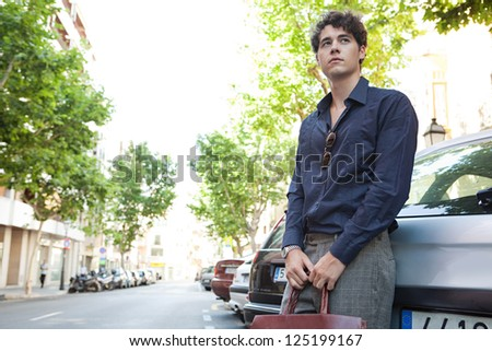 Young relaxed businessman leaning on a car, waiting while holding his leather briefcase and wearing elegant clothes.