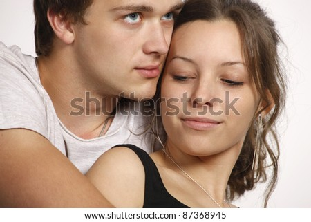 Young romancing couple on white background