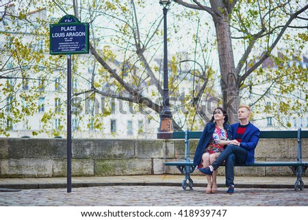 Young romantic couple sitting together on a bench on a Parisian street
