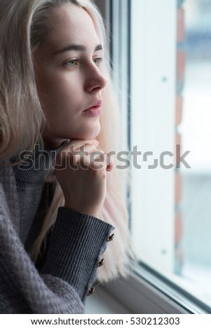 Young sad blonde woman with green coloured eyes and without makeup is looking out of window