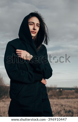 Young sad woman walking on the field in windy weather against the gray sky