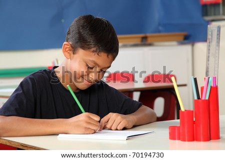 Young school boy age ten writing at his classroom desk
