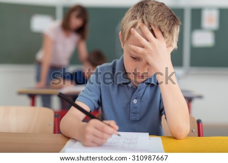 Young schoolboy hard at work in the classroom sitting with his head on his hand reading and writing notes on sheets of white paper