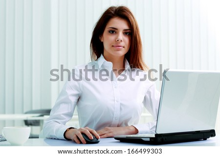 Young serious businesswoman sitting at the table with laptop in office