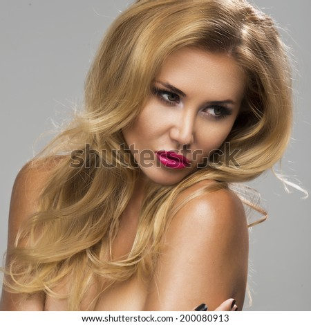 Young sexy blond woman without lingerie with pink lips posing on studio