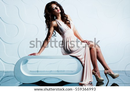Young sexy brunette woman sitting in modern interior with floor reflection
