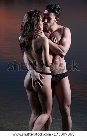 Young sexy couple on beach with sunset in background