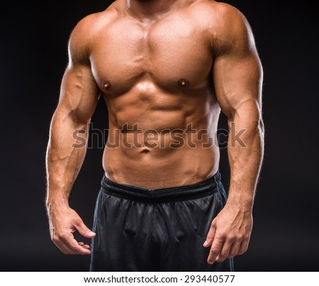 Young sexy handsome athletic man with naked torso on dark background.