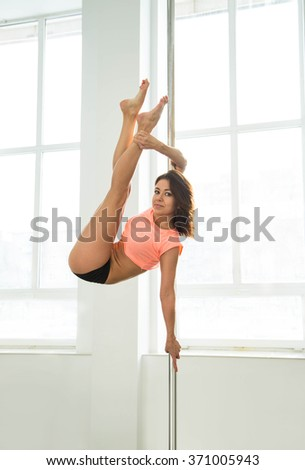 Young sexy pole dance woman. Bright white colors.