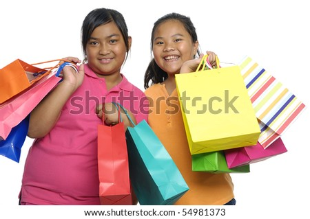 young sister girl with colorful bags isolated in white