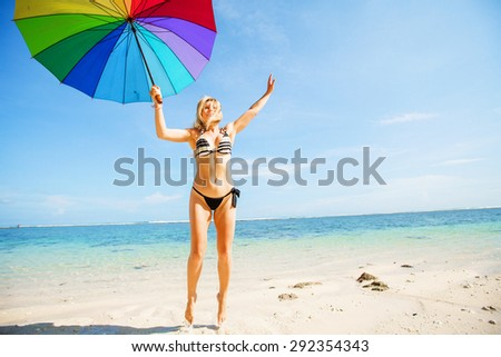 Young skinny girl in blue shorts with colourful rainbow umbrella jumps on the beach with clear blue sky and ocean on background