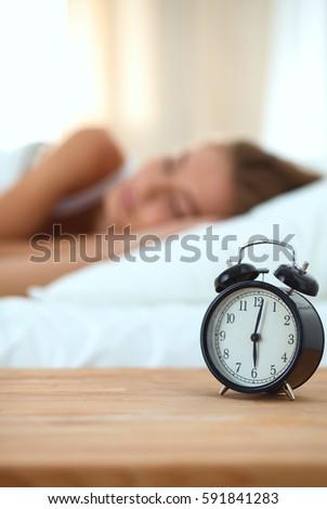 bedroom alarm clock. Young sleeping woman and alarm clock in bedroom at home Sleeping Woman Alarm Clock Bedroom Stock Photo 70778032
