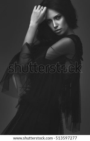 Young slim girl in black sexy fashionable dress. posing in the studio. long black hair