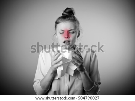 Young slim woman is sneezing. Symptoms concept. Grey and red colors.