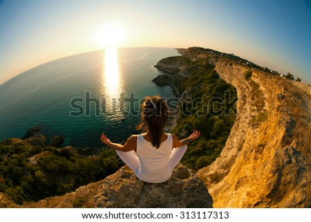 Young slim Yoga woman in zen meditating in warrior pose relaxing outside on top of mountains and sea on sunrise or sunset. Asian fitness model doing yoga on blue sky and blue sea background.