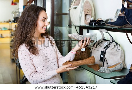 Young smiling beautiful woman shopping at fashion shoe store