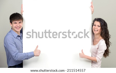 Young smiling boy and girl with white placard. Over light background.