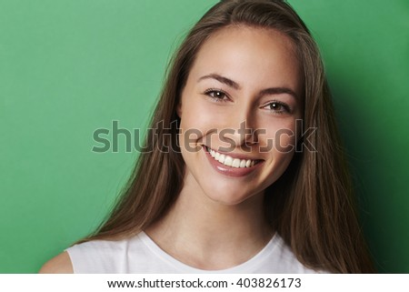 Young smiling brunette against green background