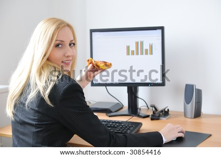 Young smiling business person working with computer eating pizza