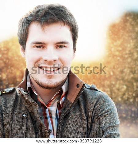 Young smiling handsome man outdoor winter colorful portrait