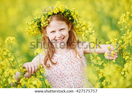 young smiling little girl with flower garland at yellow green rape seed meadow expressing joy