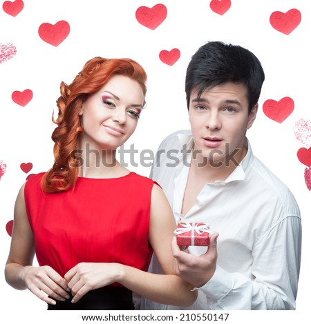 young smiling man and woman in red dress holding small red gift