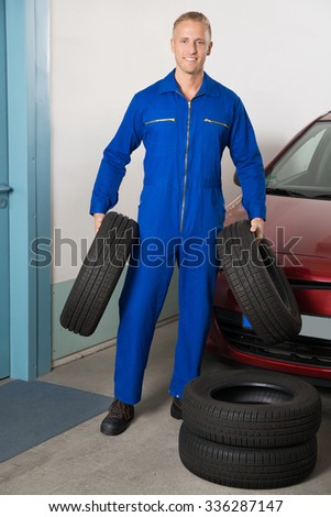 Young Smiling Mechanic Holding Tires Standing Near Car
