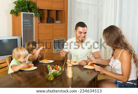 Young smiling parents with children having lunch with spaghetti at home together. Focus on man