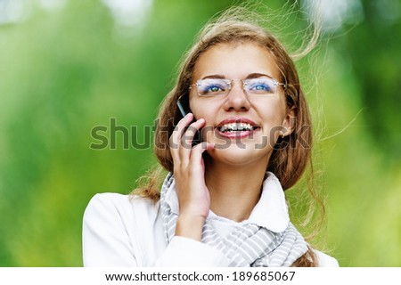 Young smiling pretty woman talking on cell phone, against background of autumn park.