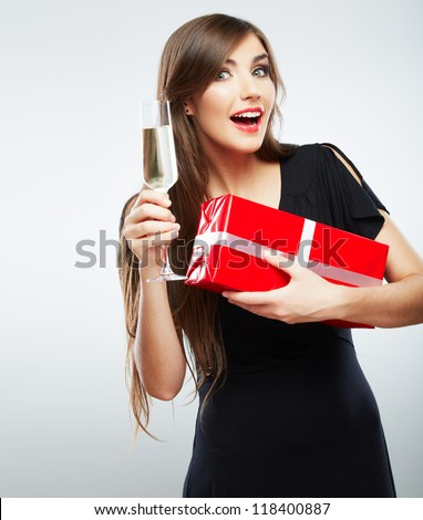 Young smiling woman hold christmas red gift box.  Isolated portrait of a beautiful girl with wine glass on studio background.