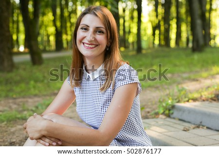 Young smiling woman in the park.