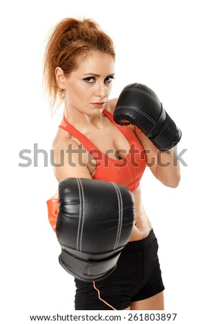 Young sporty woman wearing boxing gloves while training, isolated on white background