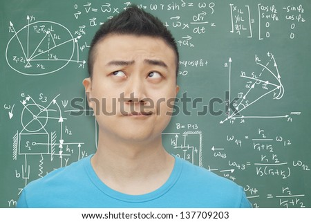 Young student in front of blackboard, making a face