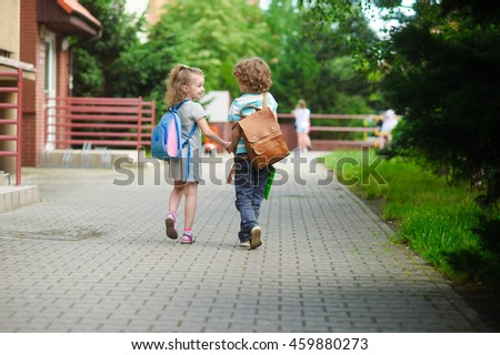 Young students, boy and girl, going to school. They hold hands. They hold hands. Children behind shoulders have satchels. Warm day in an early autumn. Back to school.