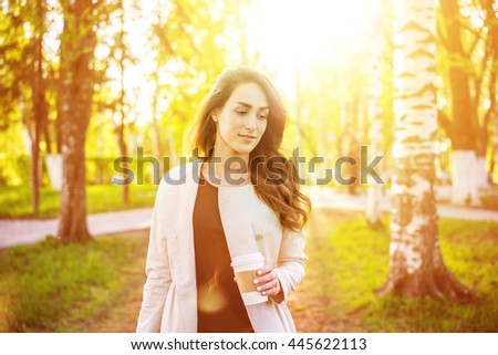 Young stylish business woman drinking coffee in a park at summer sunset.