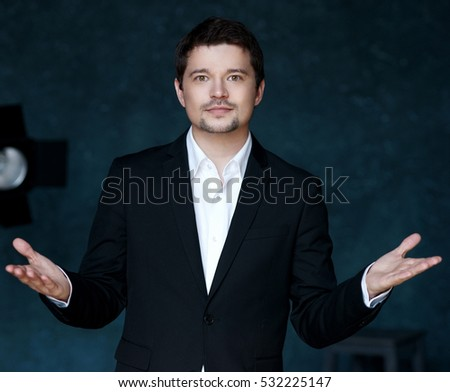 Young stylish fashionable handsome successful man standing in simple interior against blue wall and studio lightning, spreading hands and looking at you