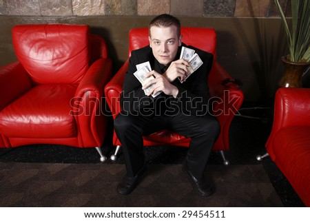 Young stylish man holding lots of cash.