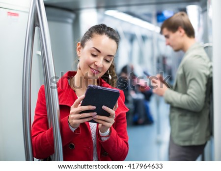 Young subway passengers busy with his the modern phones and tablet