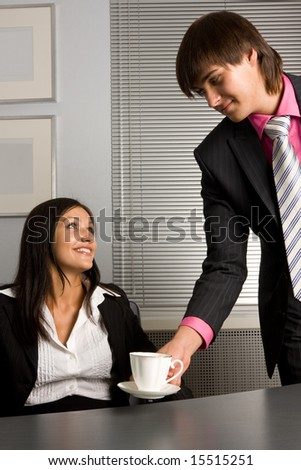 Young Successful businessman giving a cup of coffee to businesswoman
