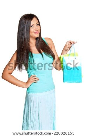 young sun-tanned woman  dressed in a turquoise shirt   holding colorful paper bags and smiling at the camera, isolated on white background